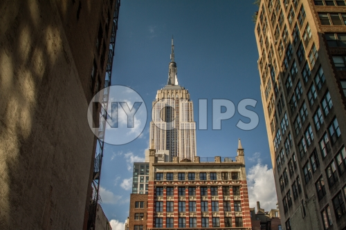 Empire State Building view from between two buildings in alley on bright sunny day