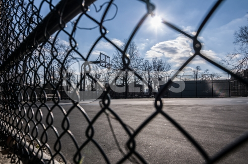 gritty fence and Harlem basketball court on sunny winter day