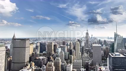 Empire State Building and MetLife skyscraper from day to night in panning timelapse - 4K Manhattan cityscape with clouds in sky overhead