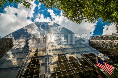 glass corporate office building and American flag - upward view