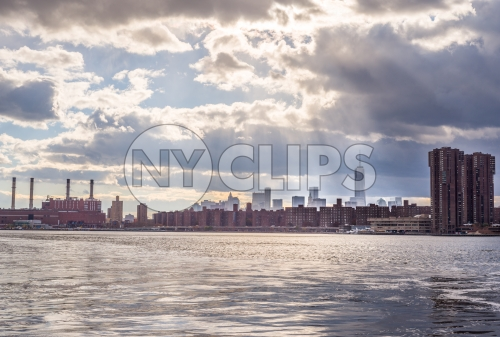 view of Freedom Tower in Manhattan skyline with red brick buildings from across river water - smoke stacks on bright sunny day with blue sky and clouds
