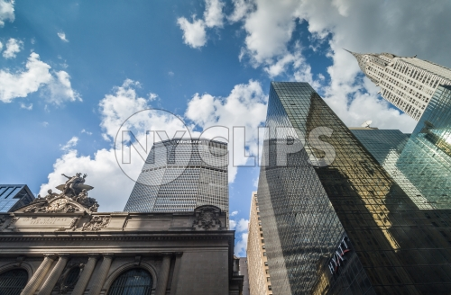 Grand Central Station Terminal with MetLife Building and Chrysler skyscraper towering over Midtown Manhattan on beautiful day - blue sky and clouds