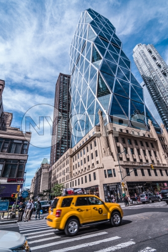 caravan taxi cab driving in traffic past famous Hearst Building in Manhattan on bright sunny day