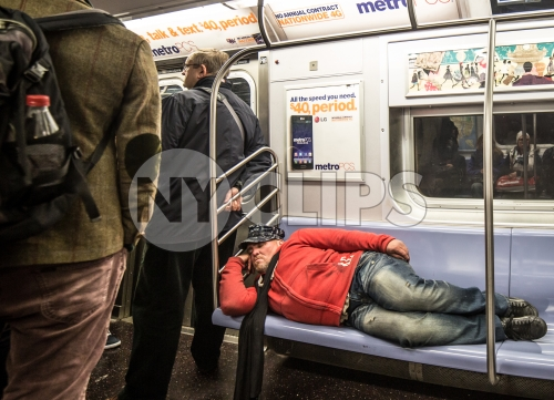 homeless man sleeping on subway train seats, taking up whole bench
