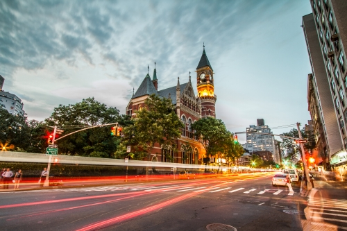 Jefferson Market Library with cars in motion blur streaks on 6th Ave in Greenwich Village in early evening - famous clock tower