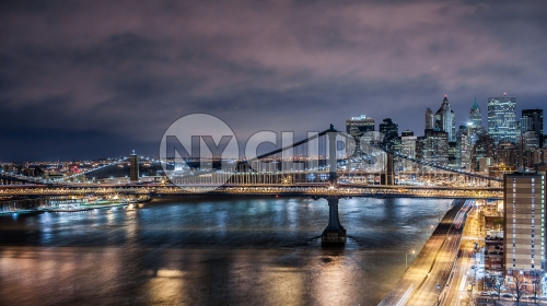 Manhattan Bridge and East River water with motion blurred cars as streaks of light on the FDR Drive highway at night in NYC