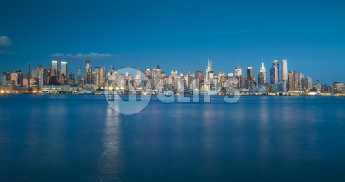Manhattan skyline from across East River early evening with blue sky and water