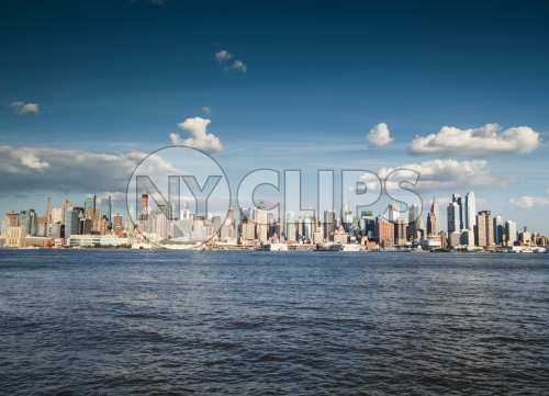 Manhattan skyline on bright sunny day from across East River water