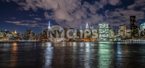 Manhattan skyline in evening with famous skyscrapers and landmarks: Empire State Building, Chrysler, United Nations and East River water