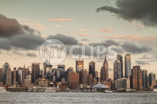 Manhattan skyline at sunset in early evening with Empire State Building and beautiful clouds overhead in NYC