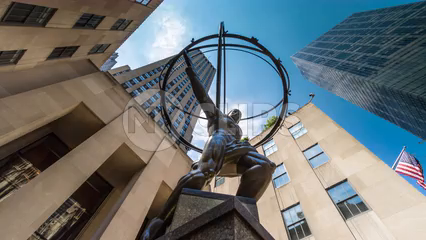 upward angle of famous Atlas statue outside Rockefeller Center with American flag - timelapse in 4K and 1080 HD NYC
