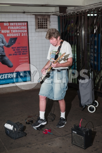 musician in shorts playing electric guitar in Manhattan subway station in summer