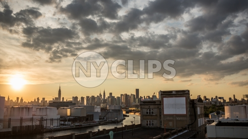 Manhattan skyline view from Brooklyn at sunset and clouds overhead in beautiful sky