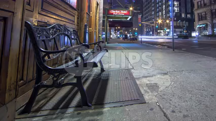 pulling back slowly from bench on Manhattan street outside bar at night - 4K timelapse