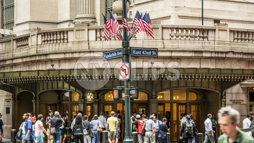 American flags on corner of East 42nd st outside Grand Central Station Terminal in Midtown Manhattan - people on crowded street on summer day