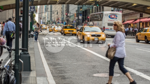 woman crossing street in Midtown outside Grand Central Station with taxi cabs driving in Manhattan