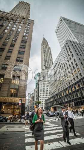 Chrysler Building towering over Midtown Manhattan - woman on smartphone crossing street on cloudy summer or spring day