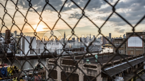 Manhattan skyline view through Brooklyn fence at sunset in NYC