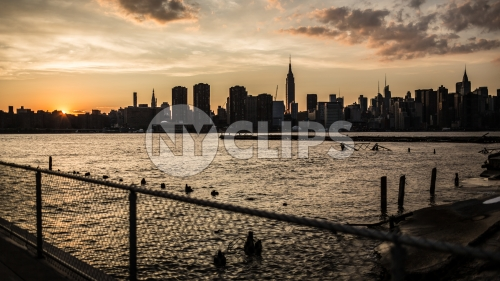 Manhattan skyline silhouette view from across East River with fence