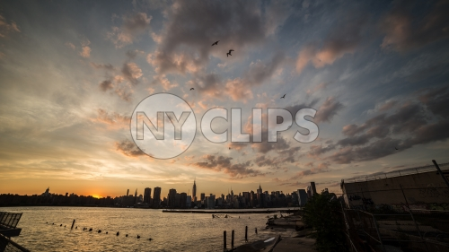Manhattan skyline silhouette with birds flying in beautiful orange sunset sky in early evening over East River water in NYC