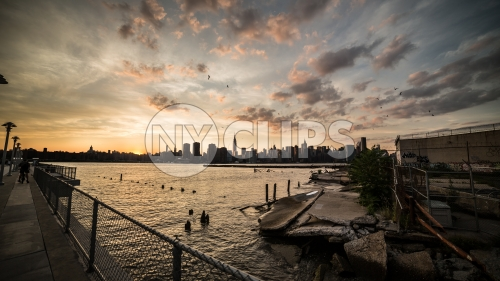 Manhattan skyline view from Brooklyn with birds flying in sky and wood dowels in East River water at sunset
