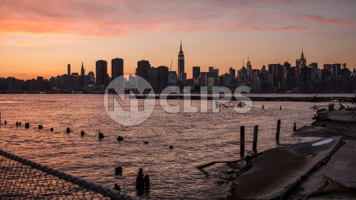 Manhattan skyline with Empire State Building silhouette view from Brooklyn across East River with wood dowels in water - early evening pink orange and purple sunset in NYC