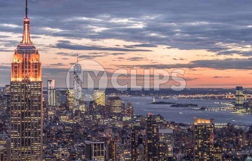 Empire State Building and Freedom Tower at sunset - famous skyscrapers in Manhattan at night with East River in distance in NYC
