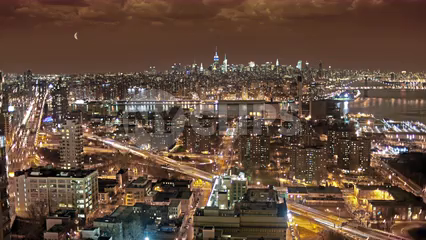 Manhattan skyline from Brooklyn  at night - high view with moon in burgundy sky in New York City