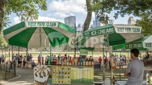 Central Park on summer day - ice cream vendor umbrella - baseball field with fence