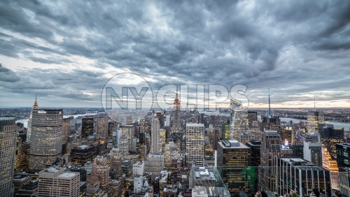 Empire State Building and Manhattan skyscrapers from high view with cold blue clouds overhead in early evening