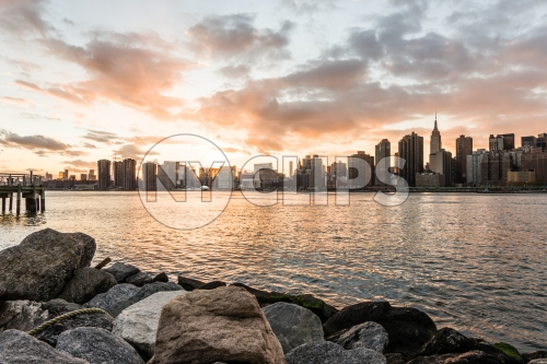 Manhattan skyline viewed from Brooklyn with rocks in foreground at sunset - beautiful orange sky and clouds over East River water