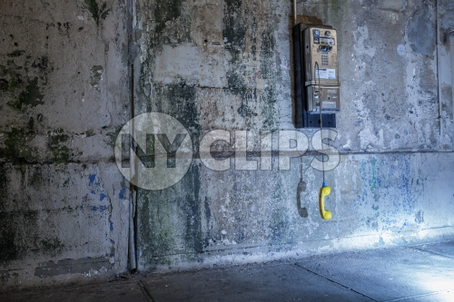 dangling public pay phone off the hook against dirty gritty wall in Brooklyn subway station