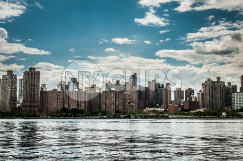red brick buildings in Queens skyline across East River on bright sunny day, blue sky and clouds