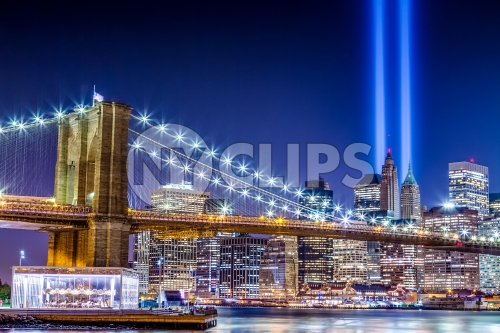 911 memorial lights, beams over Manhattan skyline with buildings and skyscrapers and Brooklyn Bridge lit up at night - carousel on East River