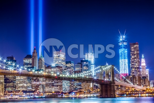 Brooklyn Bridge and Freedom Tower at night with 911 beams over city skyline - September 11th memorial lights
