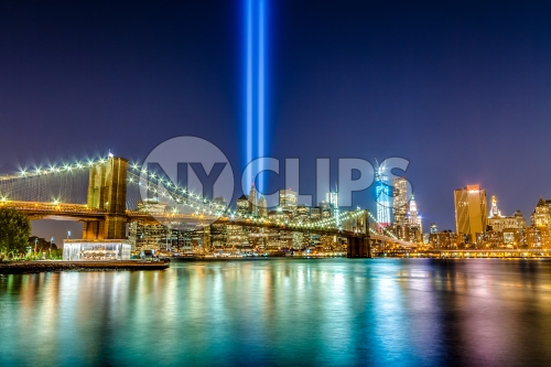 East River with 911 beams and Brooklyn Bridge reflecting off water, Manhattan skyline in background at night