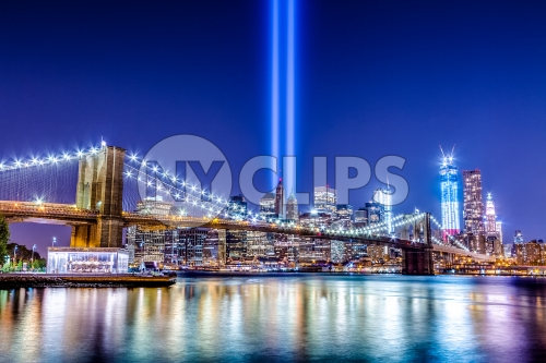 beautiful HDR night shot of Brooklyn Bridge and Manhattan skyline with city lights reflecting off East River