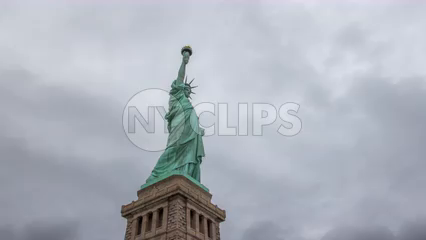 Statue of Liberty with base on foggy day - 4K upward side angle timelapse in New York City
