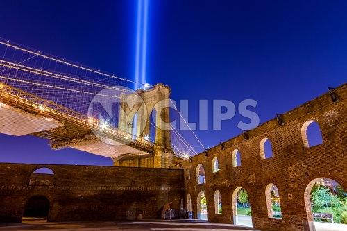abandoned gritty park at night with Brooklyn Bridge and 911 lights - beams in night sky