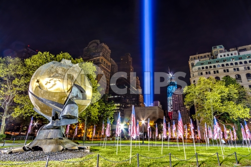 Battery Park 911 memorial beams with American flags at night