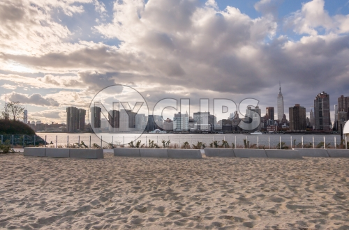 Manhattan skyline from sand - beach in Brooklyn with beautiful blue sky and clouds on summer day