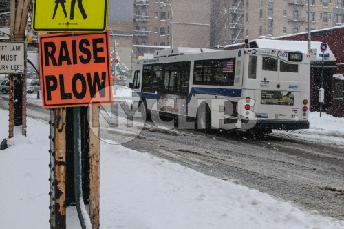 raise plow sign in winter - snowing in Manhattan - MTA bus driving on snow in winter - slush in street