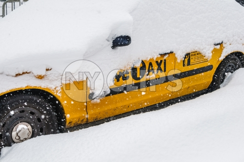 taxi cab covered in snow - snowing in winter storm