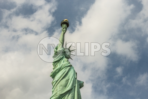 Statue of Liberty from side - medium shot - bright green over blue daytime sky with clouds