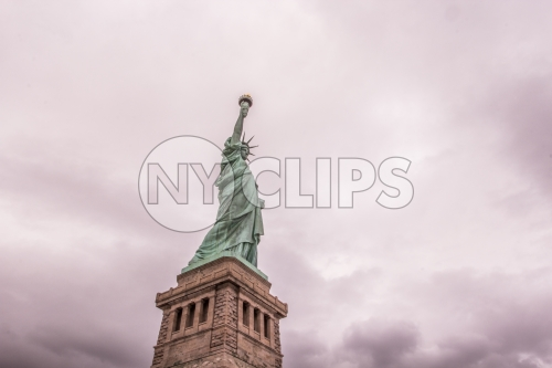 Statue of Liberty - full shot head to toe with base over pink cloudy sky