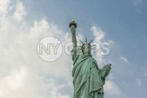 Statue of Liberty - medium shot from waist up over blue sky with clouds on bright day