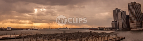 wide shot of East River at sunset with Statue of Liberty in distance - orange sky in early evening