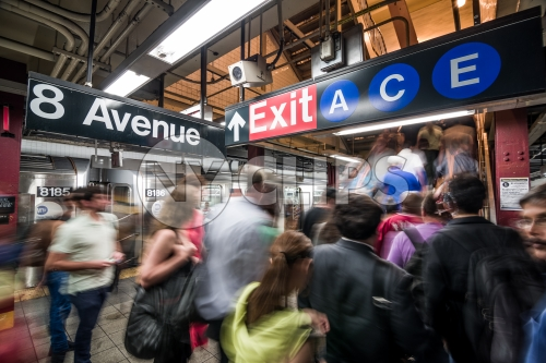 subway station - busy platform with people in motion blur on 8th Ave with A C and E exit sign in summer