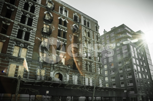 gritty tenement building with graffiti and fire escapes in Harlem, Uptown Manhattan architecture in poor neighborhood