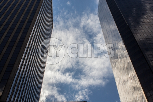 two corporate office buildings - glass windows with reflections of sky and clouds